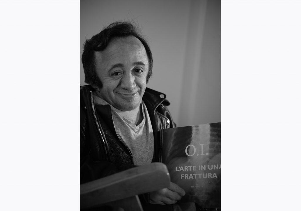 Fabiano Lioi è l'autore di O.I. L'arte in una frattura. Stampiamo insieme il libro con la campagna di crowdfunding. In questa foto tiene in mano la prova stampa del libro e guarda sorridente in macchina.