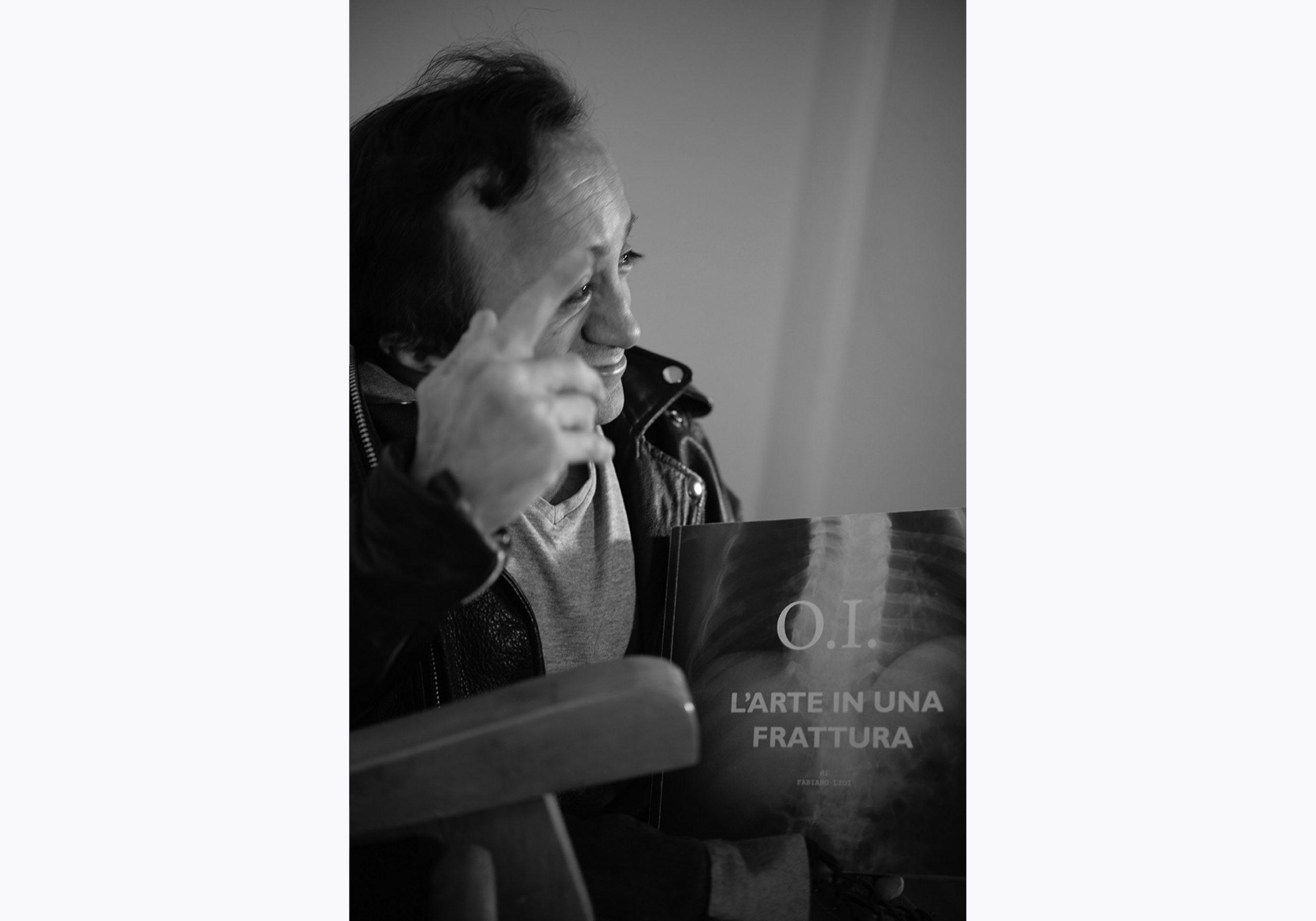 Fabiano Lioi è l'autore di O.I. L'arte in una frattura. Stampiamo insieme il libro con la campagna di crowdfunding. In questa foto punta con l'indice della mano destra verso l'alto, sorpreso in un movimento leggero mentre racconta una parte del progetto di crowdfunding.