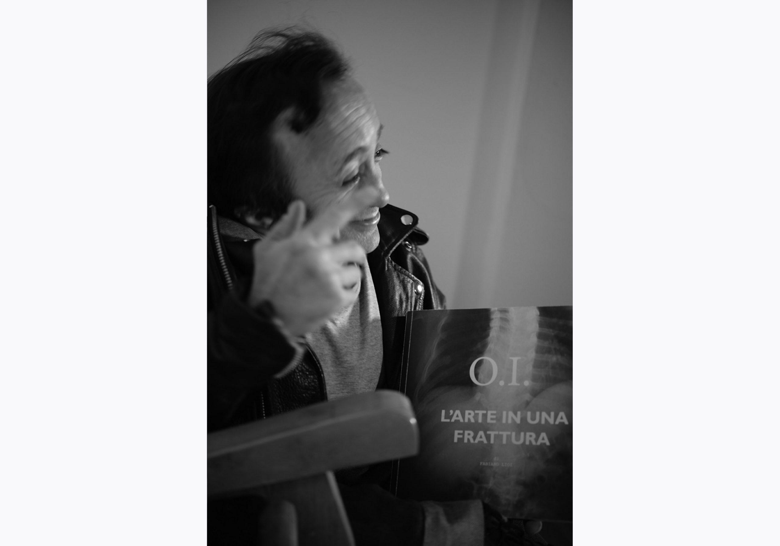 Fabiano Lioi è l'autore di O.I. L'arte in una frattura. Stampiamo insieme il libro con la campagna di crowdfunding. In questa foto sorride con la prova stampa del suo libro in mano mentre racconta una parte del progetto di crowdfunding.