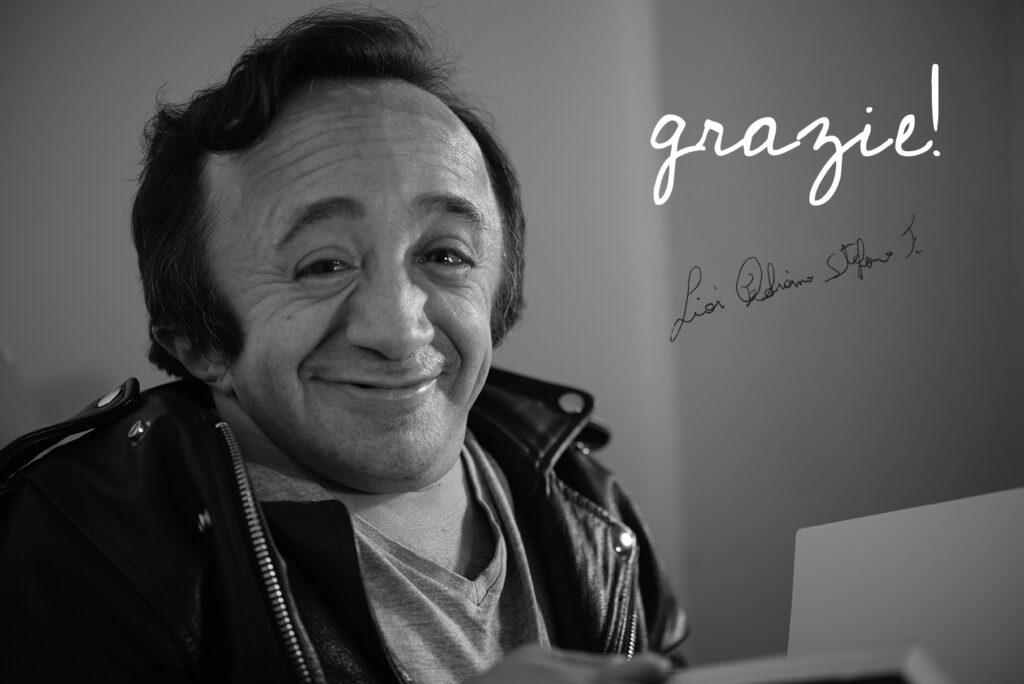 """Nell'immagine Fabiano Lioi guarda sorridente in camera, mentre sul lato destro è riportata la scritta """"grazie!"""" e la firma dell'autore: questa pagina infatti è riservata ai ringraziamenti verso tutte le persone che hanno partecipato, in qualsiasi modo, alla campagna di crowdfunding per stampare O.I. L'arte in una frattura."""
